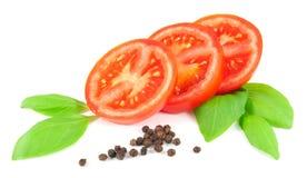 Τεμαχισμένη ντομάτα με τα φύλλα βασιλικού και το μαύρο πιπέρι Στοκ φωτογραφία με δικαίωμα ελεύθερης χρήσης