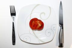 Τεμαχισμένη ντομάτα σε ένα πιάτο στο άσπρο υπόβαθρο Στοκ φωτογραφία με δικαίωμα ελεύθερης χρήσης