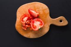 Τεμαχισμένη ντομάτα στον ξύλινο πίνακα στο μαύρο υπόβαθρο Στοκ Εικόνες