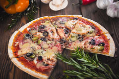 Τεμαχισμένη νόστιμη φρέσκια πίτσα με τα μανιτάρια και λουκάνικο σε ένα ξύλινο υπόβαθρο Στοκ Εικόνες