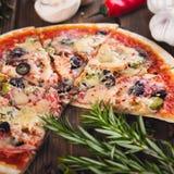Τεμαχισμένη νόστιμη φρέσκια πίτσα με τα μανιτάρια και λουκάνικο σε ένα ξύλινο υπόβαθρο Στοκ εικόνα με δικαίωμα ελεύθερης χρήσης