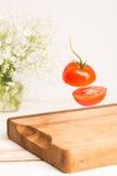Τεμαχισμένη ολόκληρη ντομάτα που πετά επάνω από έναν ξύλινο τεμαχίζοντας πίνακα Στοκ Εικόνες