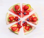 Τεμαχισμένη πίτσα καρπουζιών με τα φρούτα και τα μούρα στο άσπρο ξύλινο υπόβαθρο, τοπ άποψη τρόφιμα υγιή Στοκ Εικόνα