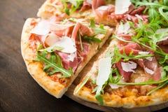 Τεμαχισμένη πίτσα με το ζαμπόν της Πάρμας prosciutto, το arugula & x28 σαλάτα rocket& x29  και παρμεζάνα σκοτεινό ξύλινο στενό σε Στοκ Φωτογραφία