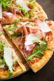 Τεμαχισμένη πίτσα με το prosciutto & x28 Πάρμα ham& x29 , arugula & x28 σαλάτα rocket& x29  και παρμεζάνα στο σκοτεινό ξύλινο υπό Στοκ φωτογραφία με δικαίωμα ελεύθερης χρήσης