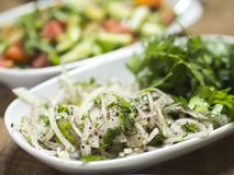 Τεμαχισμένη σαλάτα κρεμμυδιών στο πιάτο να δειπνήσει στον πίνακα υγιής και οργανικός χορτοφάγος πίνακας στοκ φωτογραφίες