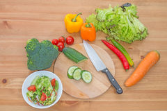 Τεμαχισμένη σαλάτα και ολόκληρα φρέσκα λαχανικά στον ξύλινο πίνακα Τοπ όψη Στοκ Εικόνες