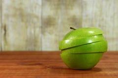 Τεμαχισμένη φρούτα συνεδρίαση σε μια ξύλινη επιφάνεια Στοκ Φωτογραφία
