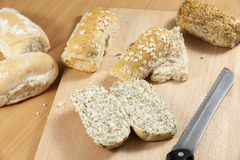 Τεμαχισμένος ρόλος ψωμιού σπόρου ηλίανθων και παπαρουνών breadboard στοκ εικόνα
