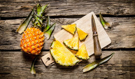 Τεμαχισμένος φρέσκος ανανάς με ένα μαχαίρι σε έναν τεμαχίζοντας πίνακα Στοκ Φωτογραφίες