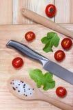 Τεμαχισμένο αγγούρι, ντομάτες κερασιών, καρύκευμα στον ξύλινο τέμνοντα πίνακα τρόφιμα έννοιας υγιή Στοκ Φωτογραφίες