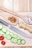 Τεμαχισμένο αγγούρι, ντομάτες κερασιών, καρύκευμα στον ξύλινο τέμνοντα πίνακα τρόφιμα έννοιας υγιή Στοκ Εικόνα