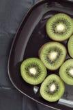 Τεμαχισμένο ακτινίδιο σε ένα μαύρο πιάτο Στοκ Εικόνες