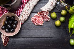 Τεμαχισμένο ιταλικό σαλάμι με το πράσινο και μαύρο antipasti ελιών και κόκκινο κρασί στο μαύρο ξύλινο υπόβαθρο, τοπ άποψη, θέση γ Στοκ φωτογραφία με δικαίωμα ελεύθερης χρήσης