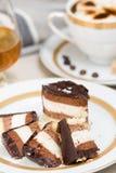 Τεμαχισμένο κέικ, cofee και κονιάκ σοκολάτας στο υπόβαθρο Στοκ Εικόνες