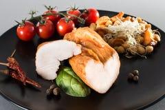 Τεμαχισμένο καπνισμένο στήθος κοτόπουλου στο μαύρο πιάτο με τα λαχανικά επάνω Στοκ Φωτογραφίες