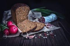 Τεμαχισμένο καφετί ψωμί, σαλάμι, ραδίκι, σκόρδο, πράσινα κρεμμύδια και ξηρός Στοκ Εικόνα