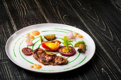 Τεμαχισμένο κρέας με τα φρέσκα χορτάρια, τα λαχανικά και τα καρυκεύματα σε ένα άσπρο πιάτο σε ένα μαύρο ξύλινο υπόβαθρο, τοπ άποψ Στοκ Εικόνες