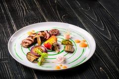 Τεμαχισμένο κρέας με τα φρέσκα χορτάρια, τα λαχανικά και τα καρυκεύματα σε ένα άσπρο πιάτο σε ένα μαύρο ξύλινο υπόβαθρο, τοπ άποψ Στοκ Φωτογραφία