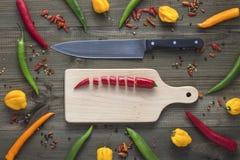 Τεμαχισμένο πιπέρι τσίλι του Cayenne στον τέμνοντα πίνακα με τα πιπέρια τσίλι μαχαιριών και του Cayenne, πιπέρια habanero, πιπέρι Στοκ Φωτογραφία