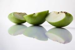 Τεμαχισμένο πράσινο μήλο από την πλευρά με την αντανάκλαση στο λευκό Στοκ φωτογραφία με δικαίωμα ελεύθερης χρήσης