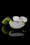 Τεμαχισμένο πράσινο μήλο από την πλευρά με την κατακόρυφο αντανάκλασης Στοκ Φωτογραφία