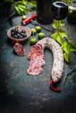Τεμαχισμένο ραβδί σαλαμιού με το antipasti, το κόκκινο κρασί και τα φύλλα σταφυλιών στο σκοτεινό εκλεκτής ποιότητας υπόβαθρο Στοκ Εικόνες