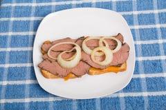 Τεμαχισμένο σάντουιτς βόειου κρέατος στην μπλε πετσέτα Στοκ Φωτογραφίες
