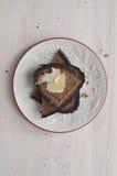 Τεμαχισμένο σκοτεινό ψωμί σίκαλης με το κομμάτι του βουτύρου Στοκ Φωτογραφίες