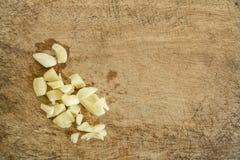 Τεμαχισμένο σκόρδο σε έναν ξύλινο Στοκ Εικόνες