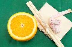 Τεμαχισμένο φρέσκο πορτοκάλι και ένας μετρητής σωμάτων Στοκ Φωτογραφία
