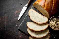 Τεμαχισμένο φρέσκο ψωμί με το μαχαίρι και το σιτάρι στο κύπελλο στοκ εικόνα με δικαίωμα ελεύθερης χρήσης