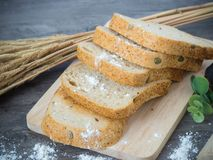 Τεμαχισμένο ψωμί δημητριακών στο ξύλο worktop και τον ξύλινο δίσκο, για το υγιές ι Στοκ εικόνες με δικαίωμα ελεύθερης χρήσης