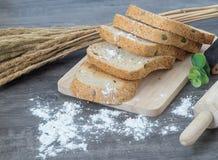 Τεμαχισμένο ψωμί δημητριακών στο ξύλο worktop και τον ξύλινο δίσκο, για το υγιές ι Στοκ Εικόνες