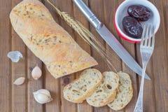 Τεμαχισμένο ψωμί, παστωμένο δαμάσκηνο στο πιάτο, πιπέρι, μαχαίρι Στοκ Φωτογραφία