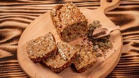 Τεμαχισμένο ψωμί σίκαλης στον τέμνοντα πίνακα Ολόκληρο ψωμί σίκαλης σιταριού με τους σπόρους Κετονογενετική χαμηλή διατροφή εξαερ στοκ φωτογραφίες με δικαίωμα ελεύθερης χρήσης