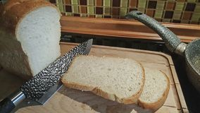 Τεμαχισμένο ψωμί σε έναν παλαιό ξύλινο πίνακα με ένα μαύρο μαχαίρι στοκ φωτογραφίες