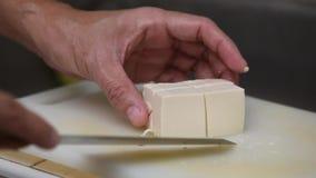 Τεμαχισμός άσπρου tofu από το μαχαίρι κουζινών στον τέμνοντα πίνακα απόθεμα βίντεο