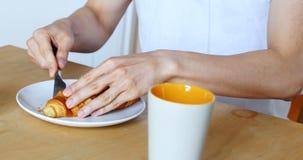 Τεμαχισμός ατόμων croissant με το μαχαίρι στο σπίτι 4k απόθεμα βίντεο