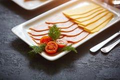 Τεμαχισμός για το πρόγευμα - τυρί και ζαμπόν Σε ένα σκοτεινό υπόβαθρο πετρών στοκ εικόνες