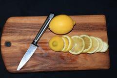 Τεμαχισμός ενός λεμονιού σε έναν ξύλινο πίνακα στοκ εικόνες