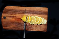 Τεμαχισμός ενός λεμονιού σε έναν ξύλινο πίνακα στοκ φωτογραφίες με δικαίωμα ελεύθερης χρήσης