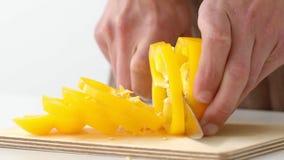 Τεμαχισμός ενός φωτεινού κίτρινου πιπεριού με το μαχαίρι σε σε αργή κίνηση απόθεμα βίντεο