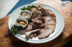 Τεμαχισμός κρέατος σε ένα μεγάλο άσπρο πιάτο που διακοσμείται με την πρασινάδα στοκ εικόνα