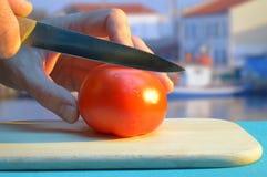 Τεμαχισμός μιας ντομάτας στον τέμνοντα πίνακα στο λιμάνι στο ηλιοβασίλεμα στοκ εικόνα