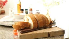 Τεμαχισμός ολόκληρου ενός ψωμιού σιταριού με ένα μαχαίρι φιλμ μικρού μήκους