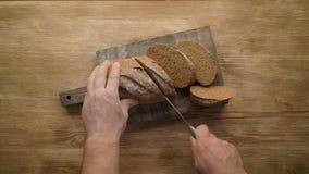 Τεμαχισμός ολόκληρου του ψωμιού σιταριού στον ξύλινο πίνακα, τοπ άποψη, απόθεμα βίντεο