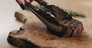 Τεμαχισμός της μέσης σπάνιας μπριζόλας λωρίδων mignon στον ξύλινο πίνακα στοκ φωτογραφίες