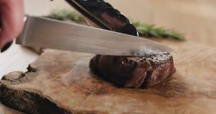 Τεμαχισμός της μέσης σπάνιας μπριζόλας λωρίδων mignon στον ξύλινο πίνακα στοκ εικόνες