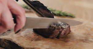 Τεμαχισμός της μέσης σπάνιας μπριζόλας λωρίδων mignon στον ξύλινο πίνακα στοκ φωτογραφία
